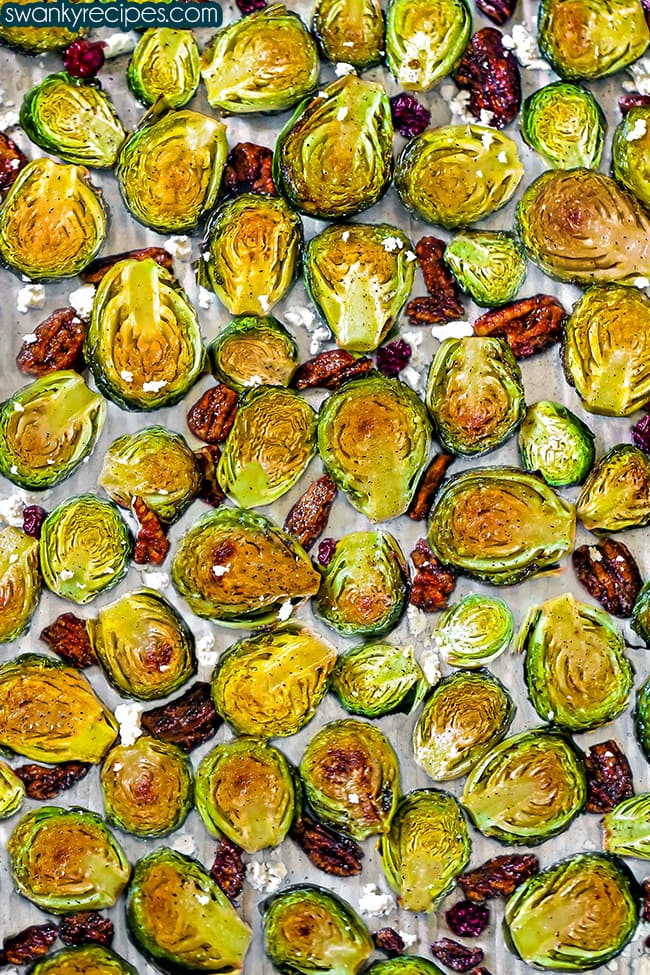 Brussels sprouts cut in half with the centers facing up on a sheet pan. Roasted in the oven with golden brown tops, pecan halves, dried cranberry pieces, and feta cheese tossed on the sheet pan.