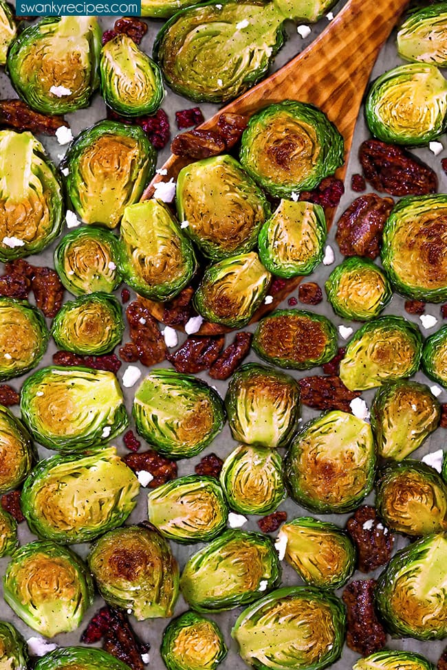 A close up of green brussels sprouts with golden yellow brown charred centers. Cut lengthwise and roasted on a sheet pan then tossed in garlic butter. Served on a wooden spoon with pieces of toasted pecans, dried cranberry pieces, and chunks of feta cheese.