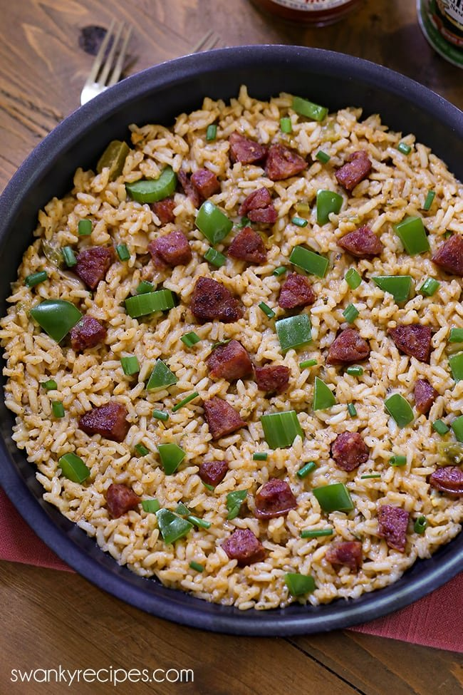 Dirty Rice - Far image of black skillet with a spread of cooked yellow brown rice, green peppers, onions, celery, and pork sausage on top. Served on a wooden board with a pink napkin.