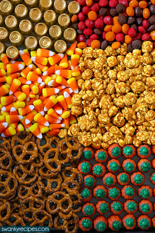 A sheet pan with pretzels, orange and green pumpkins, caramel candy corn, candy corn, m&ms and rolos in wrappers.