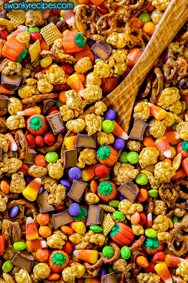 A sheet pan filled with golden caramel corn, green and orange pumpkin candy corns, classic candy corn candy, pretzels, chex cereal, rolos, and halloween m&ms with a wooden spoon scooping the mixture up.
