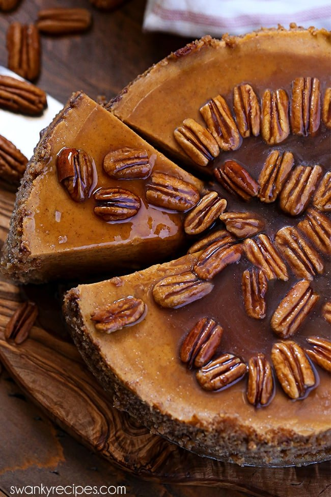 Praline Pumpkin Cheesecake - An overhead view thats slightly tilted with half the cheesecake close up in the photo frame. A slice is being lifted out of the cut center with a metal cake knife. Cheesecake is served on a wooden cutting board with a wooden board below it, too. The cheesecake has pecans in a large circle closely set together with a brown pecan praline glaze.