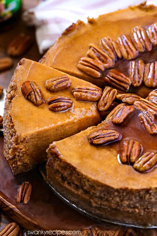 Pumpkin Praline Cheesecake - Pumpkin cheesecake with graham cracker crust with a golden orange hue and pecans in a brown glaze. A slice cut and pulled out from the center with glazed pecans on top. Served on a wooden board with praline topping dripping onto a second wooden board.