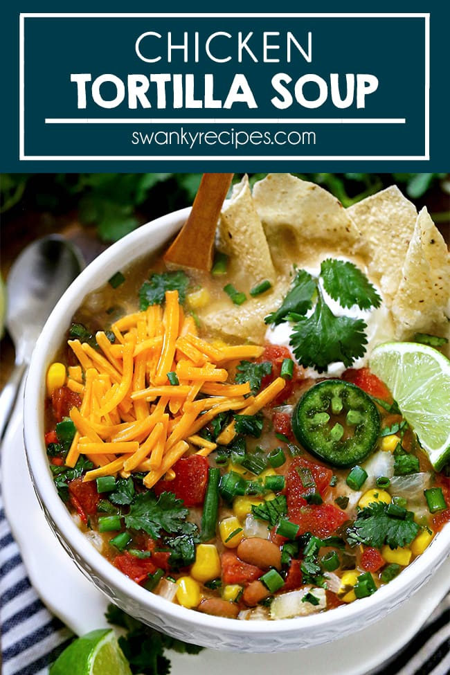 Chicken Tortilla Soup - A white soup bowl on a white plate on a white and royal blue striped napkin. Served on wooden board with a small spoon and lime slice near napkin. Soup bowl filled with a yellow red broth and topped with shredded cheddar cheese, cilantro leaves, diced tomatoes, a lime slice in corner, pinto beans, corn, green onions, and white onions sprinkled around dish. Top of dish features a wooden spoon submerged in the broth with a few tortilla chips in the soup. A dollop of sour cream with 3 cilantro leaves next to it. Text in blue border at top of images reads, Chicken Tortilla Soup.