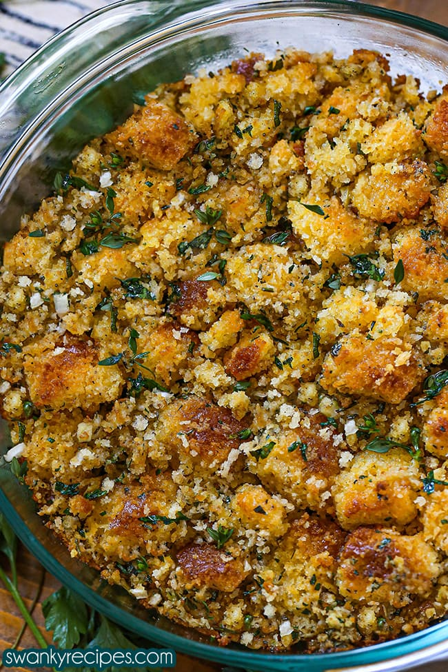 Best Cornbread Stuffing - A close up view of cornbread dressing in a round glass casserole dish with chunks of yellow cornbread toasted and tossed with chopped white onion, celery, and bell peppers and herbs in small pieces around the cornbread chunks. Served on a wooden board.