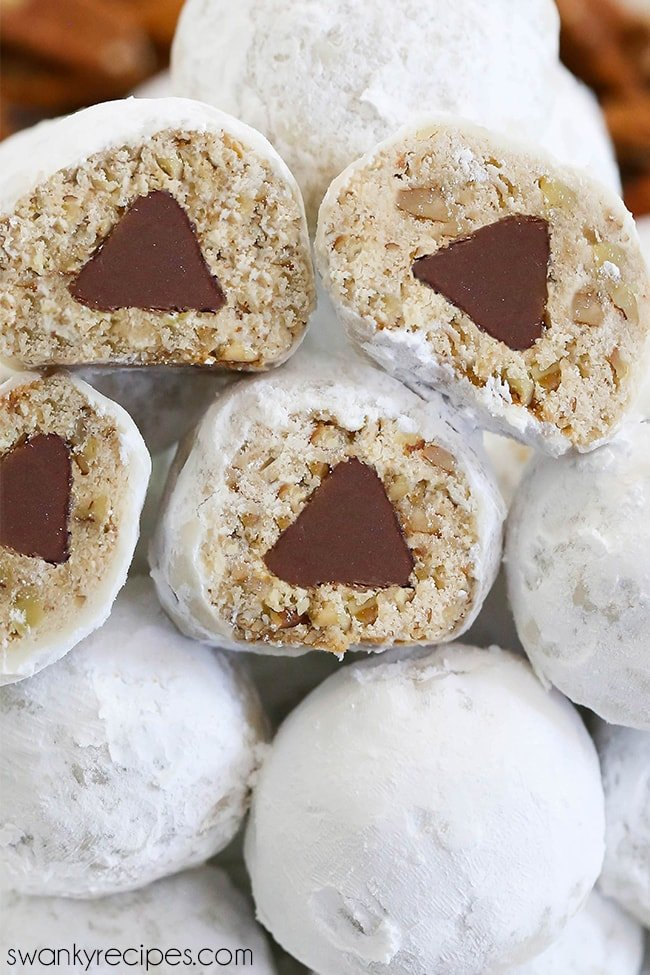 Hershey's Kiss Snowballs - A plate with white cookie dough balls rolled in powdered sugar and stacked. Four snowballs cut in half to reveal a hershey's chocolate kiss baked into the center of each ball.