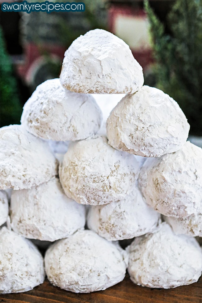 Kiss Snowball Cookie Recipe - Snowball cookie tower stack on a wooden surface. Each snowball cookie is rolled in powdered sugar then stacked to a diamond shape with one cookie at the top.