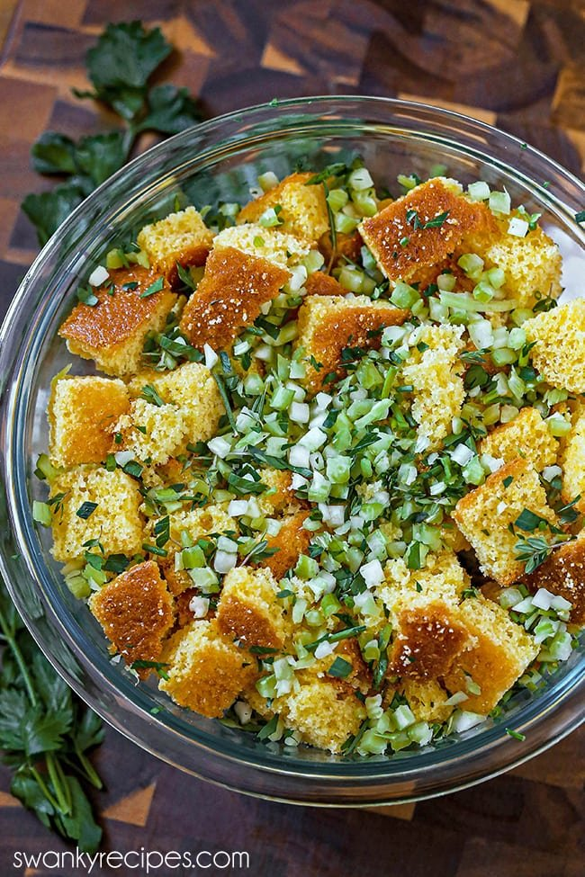 Traditional Cornbread Dressing - Homemade cornbread pieces with bell pepper, onion, celery and herbs tossed together in a bowl with broth. Serve this southern thanksgiving cornbread stuffed for the holidays. Served on a dark wooden brown cutting board in a glass bowl with parsley on the side.