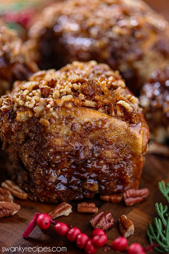 Christmas Sticky Buns Recipe - A sticky bun end on a wooden board with pecans in front of the roll. A sticky brown sauce drips down the roll with chopped pecans on top of the roll.
