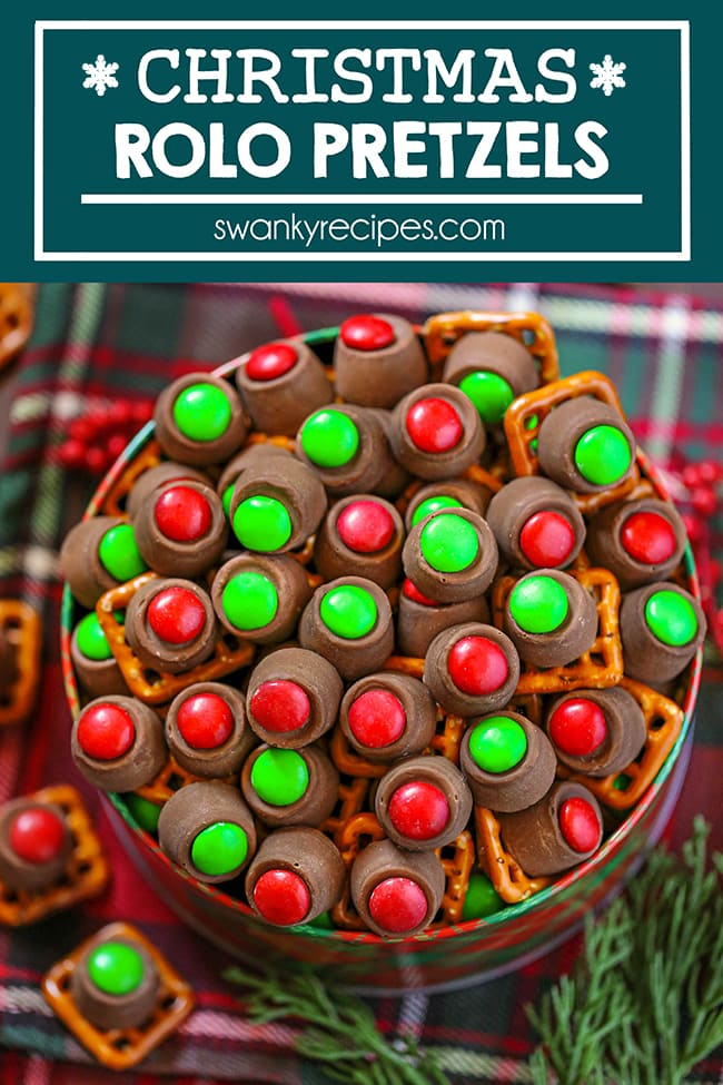 Christmas Rolo Pretzels - A far away view of rolo pretzels. Same as first photo, but further away. Overhead view of a red and green Christmas pattern on a tin filled to the brim with rolo candy pieces. Red and green M&Ms topped on a rolo candy piece with a square pretzel. Served on a red and green Christmas napkin with rolo pieces in the background and fake twigs of a spruce tree. Text in blue and white reads Christmas Rolo Pretzels.