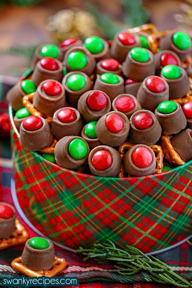 Easy Rolo Pretzel Bites - A front view of Rolo pretzels with a red/green M&M on top of a rolo candy pieces and pretzel square. Served in a red and green striped holiday tin on a wooden back drop with a Christmas color napkin.