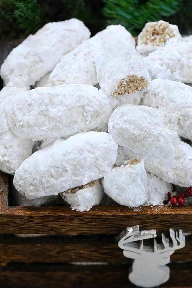 Christmas Pecan Fingers - Pecan Fingers empilhados em uma caixa de madeira e enrolados em açúcar de confeiteiro.