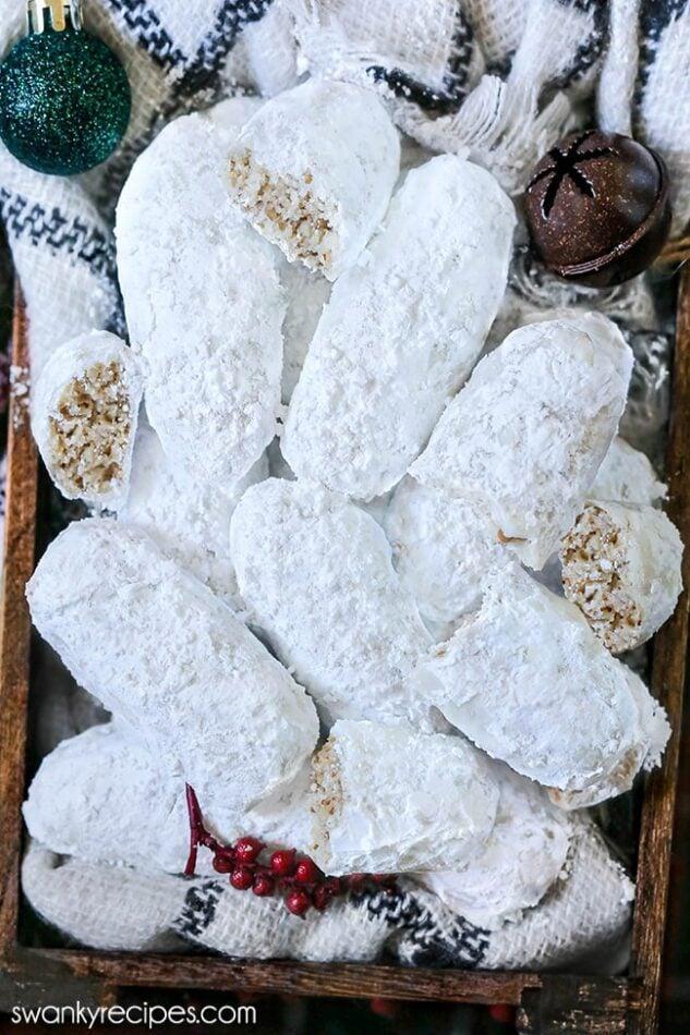 Dedos de noz-pecã fáceis - dedos de noz-pecã em uma caixa de madeira.  Uma imagem aérea dos biscoitos empilhados e dispostos com um lenço listrado branco e preto por baixo.  Um ornamento verde, um sino rústico marrom e bolas de cranberries falsas em uma caixa.