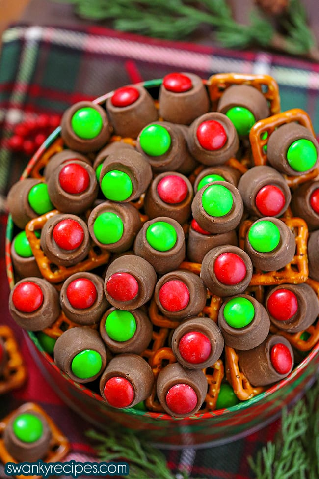 Rolo Pretzels - Overhead view of a red and green Christmas pattern on a tin filled to the brim with rolo candy pieces. Red and green M&Ms topped on a rolo candy piece with a square pretzel. Served on a red and green Christmas napkin with rolo pieces in the background.