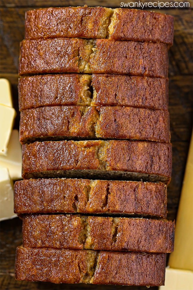Classic Banana Bread - An overhead view of golden brown banana bread slices in its classic loaf shape. Served on a wooden tray with a yellow butter knife and butter.