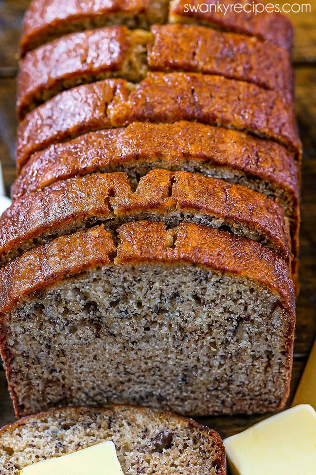 Best Banana Bread Recipe - A loaf of banana bread out of the tin served on a wooden tray. Slices of bread in a line with a moist brown batter. Severed with a butter knife to the right.