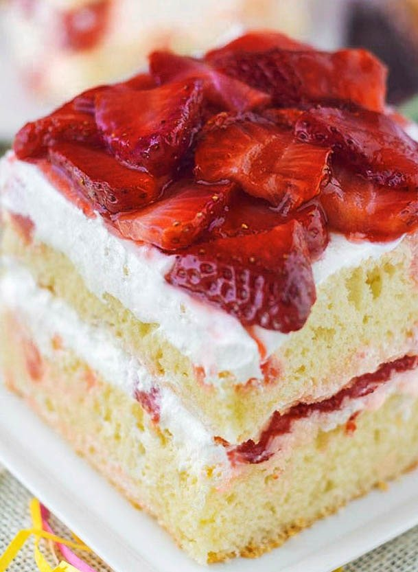 Strawberry Shortcake Cake - Strawberry shortcake recipe served on a white plate with white burlap. A decadent two layer white cake with sliced strawberries in a sugar sauce and whipped cream frosting.