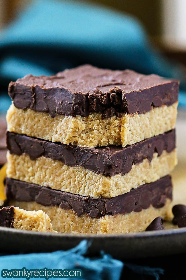 Easy Peanut Butter Bars - A stack of three peanut butter bars served on a plate. Each bar is topped with a thick layer of chocolate.