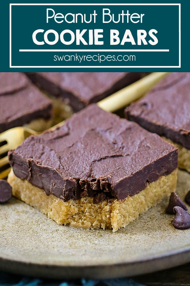 Peanut Butter Cookie Bars - Peanut Butter square served on a plate with chocolate chips to the side. A yellow fork and more dessert squares in the background.