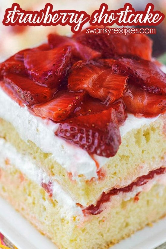 Strawberry shortcake cake on a white plate. A double layer of white cake with sliced strawberries and whipped cream filled in the center. It's topped with more sliced strawberries in juice and whipped cream. Text on top in red and white reads strawberry shortcake.