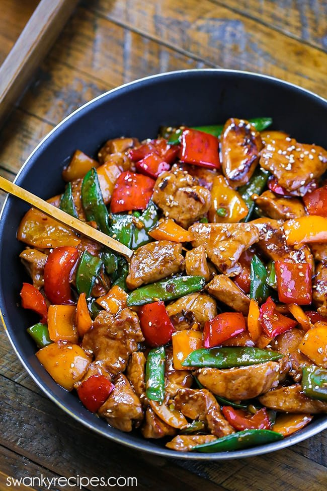Teriyaki Pork Stir Fry - A skillet loaded with pieces of pork tenderloin, colored bell peppers, and snow peas tossed in an orange sauce with a yellow spoon. Styled on a wooden tray.