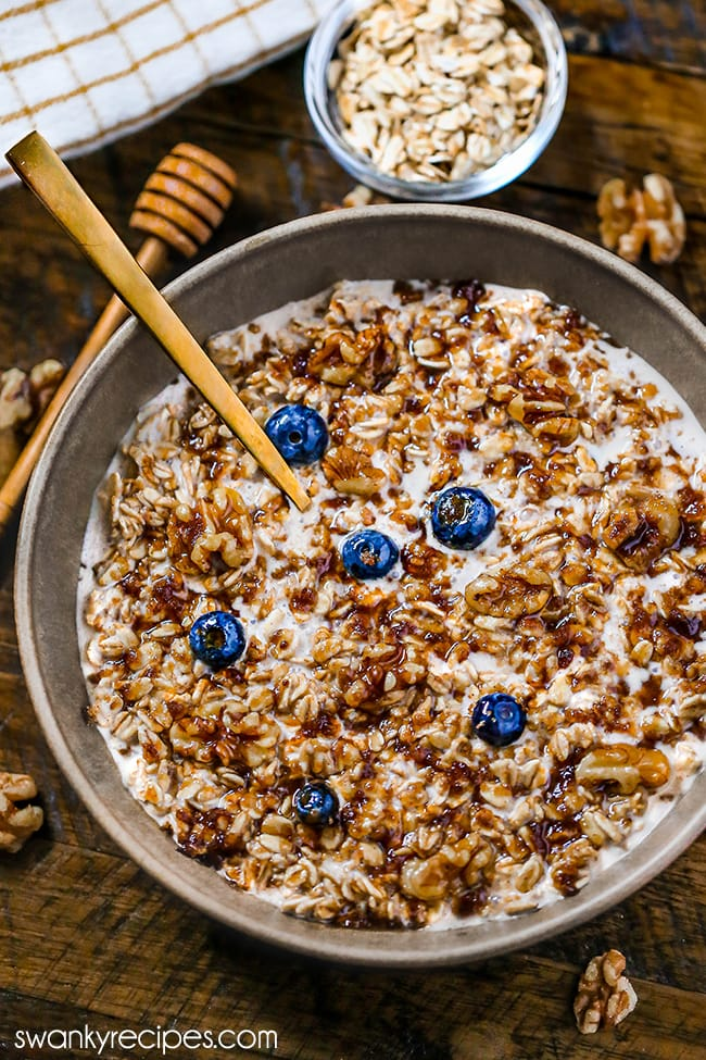 Blueberry Overnight Oats - A bowl of old-fashioned rolled oats with a drizzle of maple syrup, walnuts, and fresh blueberries. Served on a wooden board with walnuts, a small bowl of oats, and a honey dipper.