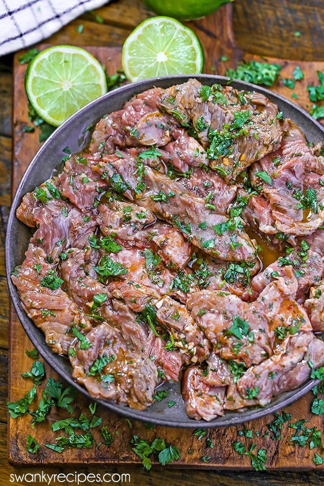 Carne Asada Marinade - Stripes of skirt steak in oil and cilantro featured on a pottery plate and wooden cutting board. Limes and cilantro scattered in the background with a white napkin.