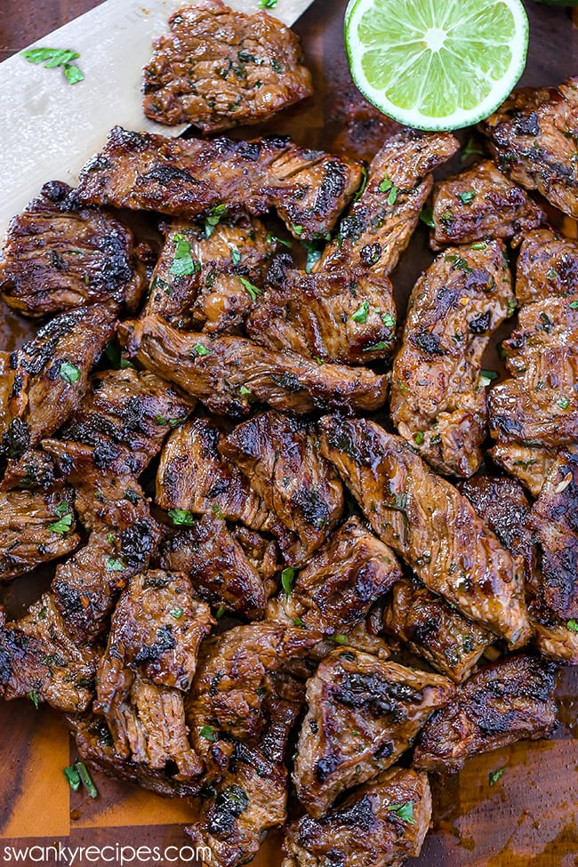 Carne Asada - Juicy seared stripes of carne asada on a wooden cutting board. Garnished with chopped cilantro.