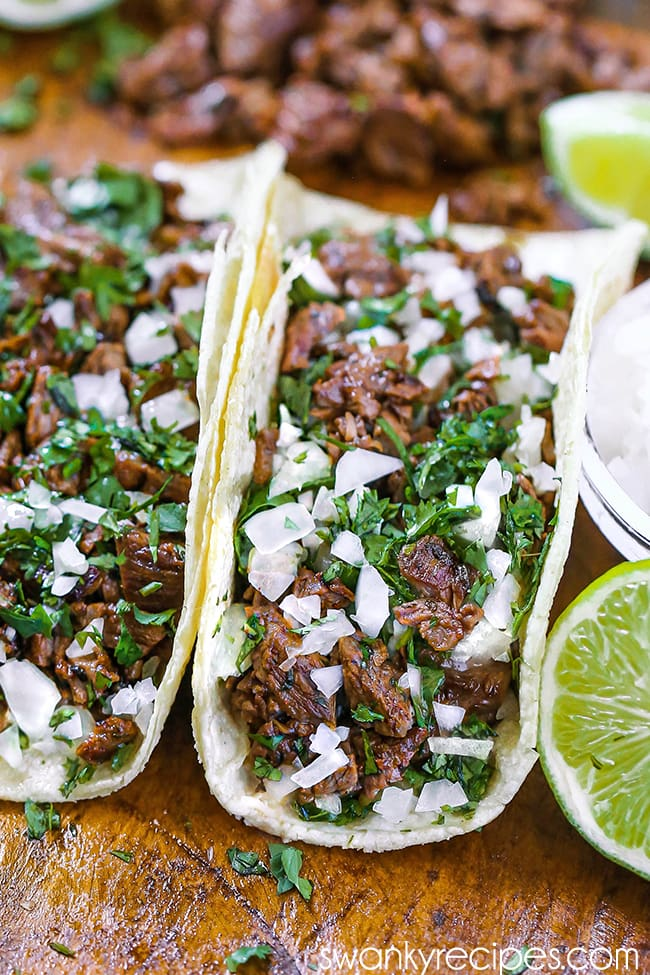 Carne Asada Tacos - Tacos filled with seared beef, cilantro, and onions. Served on a wooden cutting board with a bowl of white onions, lime slices, and chopped carne asada in the background.