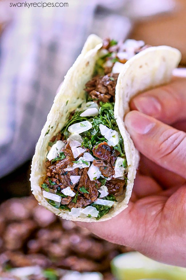 Mexican Carne Asada Tacos - Two hands holding a taco. Taco features seared and chopped beef skirt steak, chopped cilantro, and diced white onions.