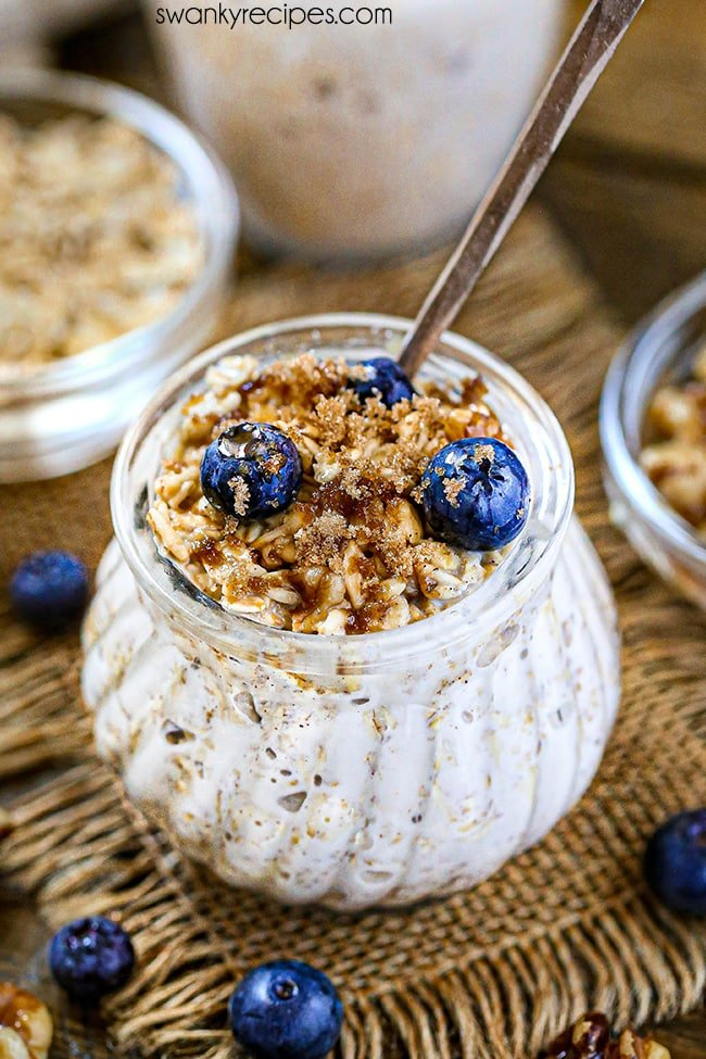 Blueberry Muffin Overnight Oats - A jar of prepared overnight oats with a thick and creamy white texture. Served in a glass jar on top of a wooden board with burlap and topped with crunchy walnuts, fresh blueberries, brown sugar, and a drizzle of maple syrup.