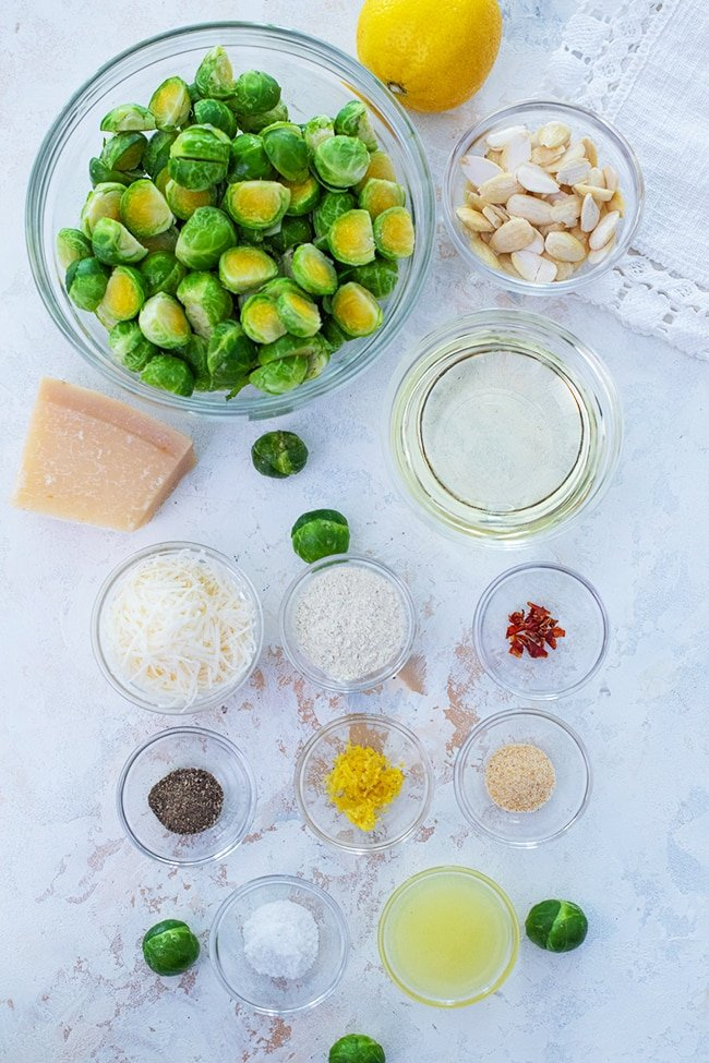 Roasted Brussels Sprouts - An overhead view of brussels sprouts ingredients. Small bowls featuring salt, lemon juice, pepper, lemon zest, garlic powder, red pepper flakes, and ranch seasoning. Larger bowls of oil, almonds, and cut brussels sprouts displayed on a white backdrop.