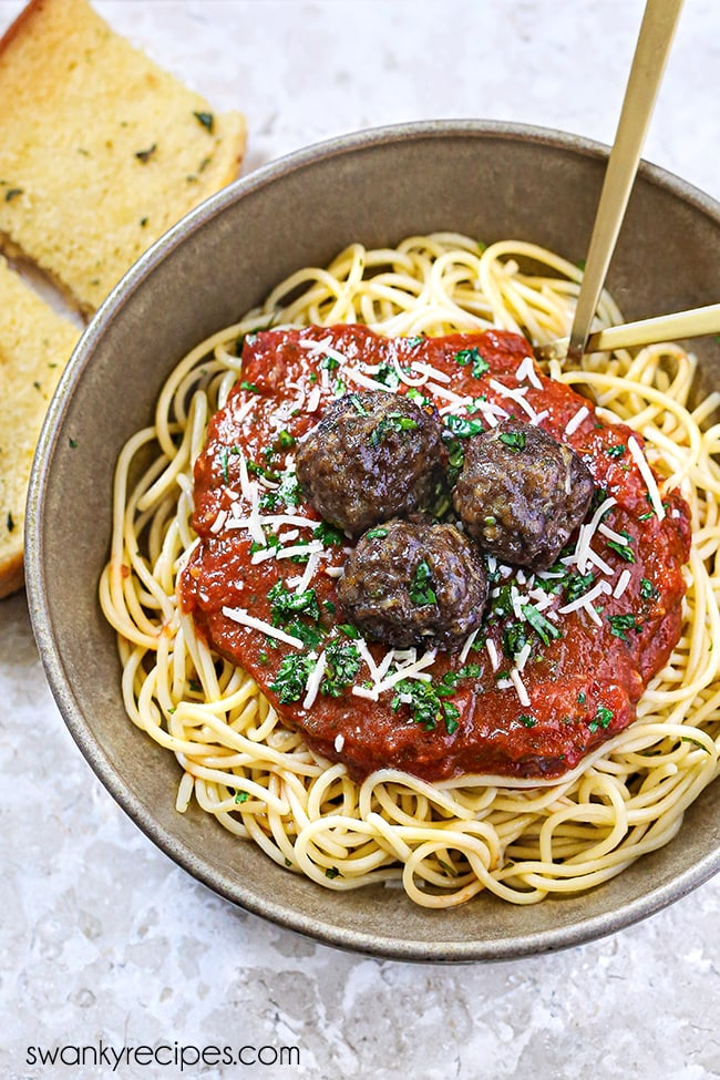 Spaghetti - A bowl of spaghetti noodles, tomato sauce, and meatballs served on a marble backdrop with a fork in bowl and garlic bread.