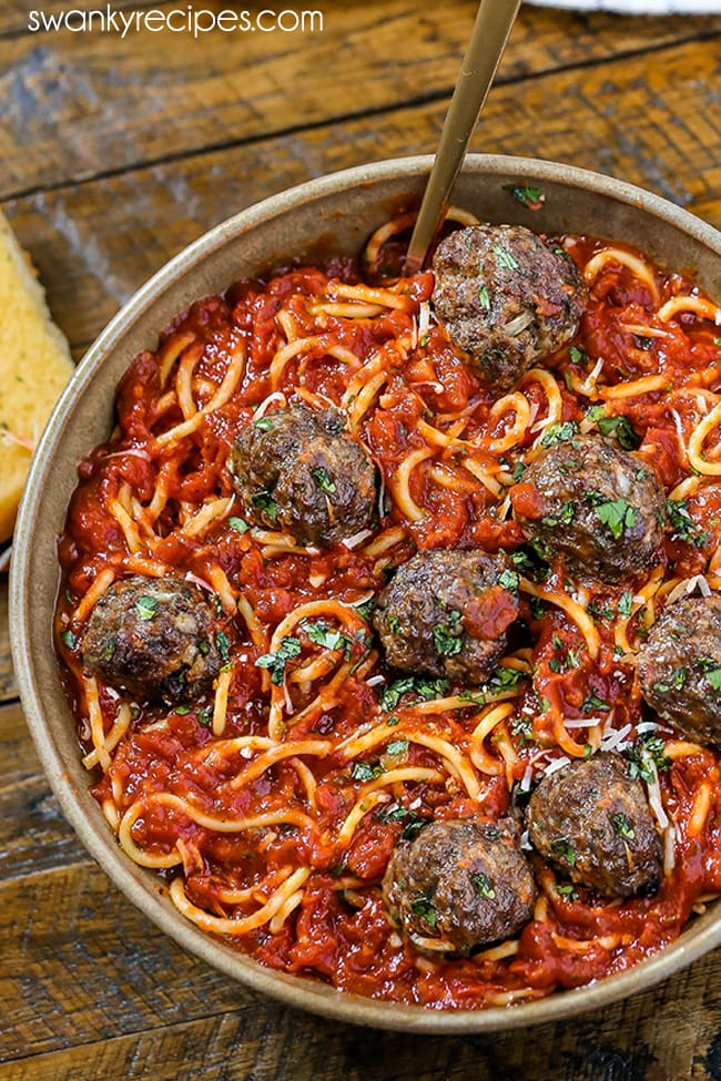 Homemade Spaghetti and Meatballs - A pottery bowl filled with spaghetti pasta noodles in a red tomato sauce with 8 meatballs. Garnished with chopped parsley and parmesan cheese on top. Served on a wooden board with a slice of garlic bread and a fork in bowl.