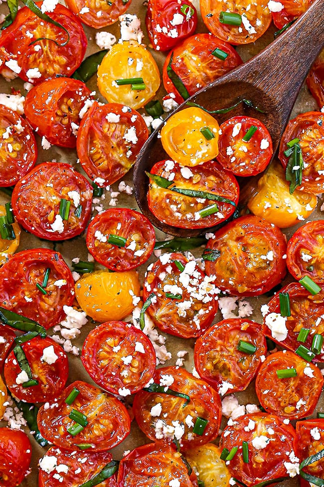 Crack Tomatoes - A close up overhead view of red cherry tomatoes and yellow currant tomatoes cut in half and roasted on a gold sheet pan. Garnished with fresh basil strands, feta cheese, and chopped chives.
