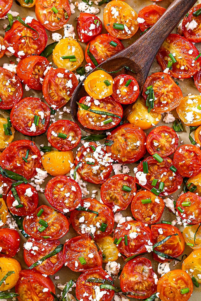 Crack Tomatoes - An overhead view of cherry tomato halves on a gold sheet pan with wooden spoon. Garnished with fresh basil strands, chives, and crumbled feta cheese.