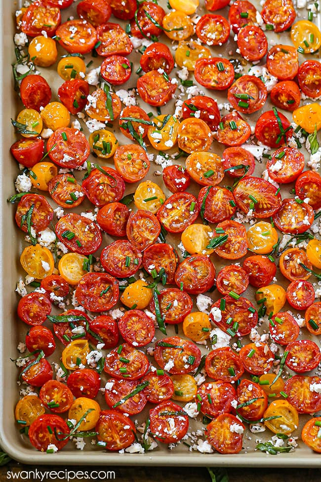 Ranch Roasted Tomatoes - A far view of cherry and currant tomato halves on a gold rimmed sheet pan. Tossed with basil, crumbled feta cheese, and chopped chives.