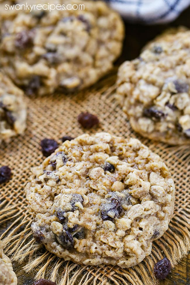 A single oatmeal raisin cookie on burlap with raisins.