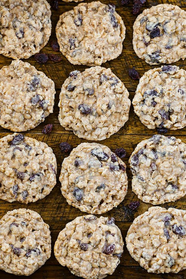 12 Oatmeal Raisin Cookies on a wooden surface with raisins.