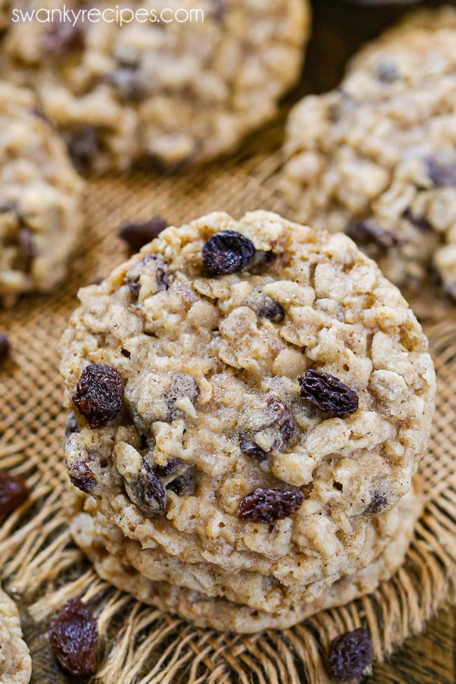 A stack of Oatmeal Raisin Cookies. A buttery cookie with oatmeal pieces and raisins on top. Served on burlap with raisins.