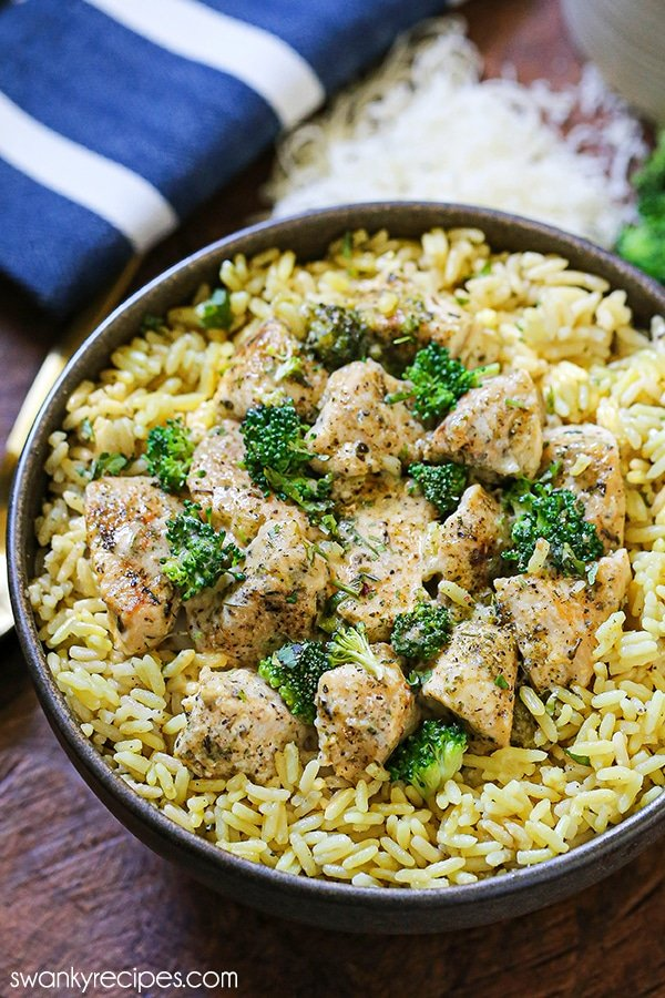 A bowl of yellow rice with tender pieces of chicken and broccoli tossed in a cream sauce. Grated parmesan cheese, broccoli florets, and a blue napkin set in the background.