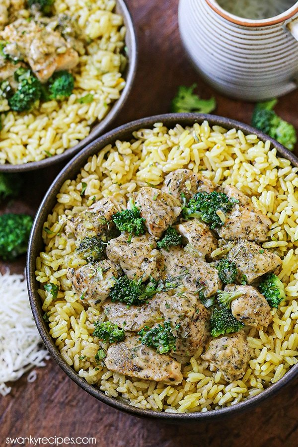 An overhead photo of chicken and broccoli pieces in a cream sauce served over rice. Background image features another prepared bowl, grated cheese, and a container.