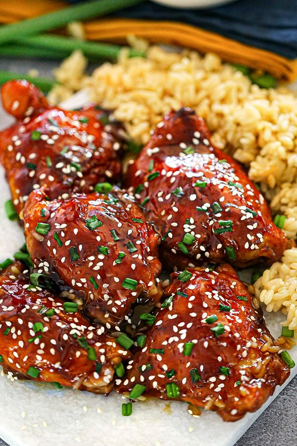 Honey Sesame Baked Chicken Thighs served on a marble platter and garnished with green onions and sesame seeds. Yellow rice and green onions in the background with a two tea towels.