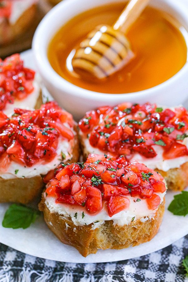 A plate of Strawberry Bruschetta with toasted slices of bread that is topped with a layer of cream cheese, freshly diced strawberries, chopped mint, and a drizzle of honey.