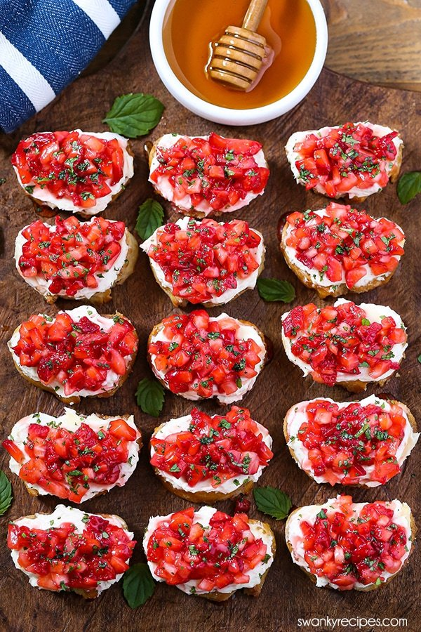 Strawberry Bruschetta arranged on a wooden platter. Fifteen slices of baguette bread topped with cream cheese, diced strawberries, and chopped mint.