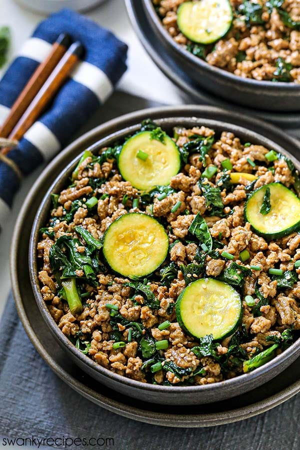 Easy Teriyaki Turkey Bowls - An overhead view of a ceramic bowl filled with ground turkey, sliced zucchini, and chopped kale with green onions. Served on a wooden white platter with a napkin and chopsticks.